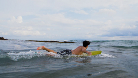 Handheld-Wide-Shot-of-Young-Surfer-Running-Into-Sea