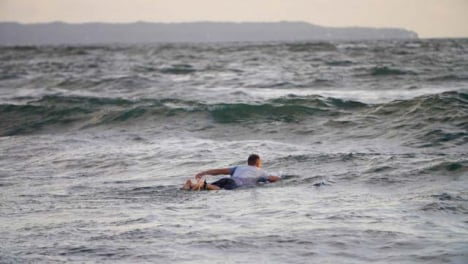 Handheld-Long-Shot-of-Surfer-Swimming-Out-to-Sea