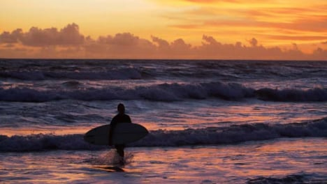 Handheld-Wide-Shot-Tracking-Surfer-Walking-Out-of-Water-at-Sunset