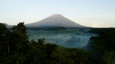 Drone-Shot-Flying-Over-Trees-Towards-Mount-Agung-Volcano