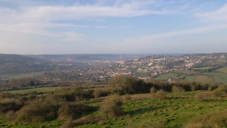 Drone-Shot-Flying-Over-Hills-Towards-City-of-Bath