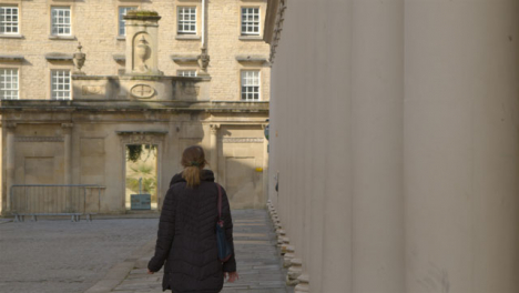 Wide-Shot-of-Person-Walking-Between-Old-Stone-Pillars-