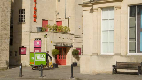 Wide-Shot-of-Delivery-Cyclist-Riding-Past-Old-Cinema-