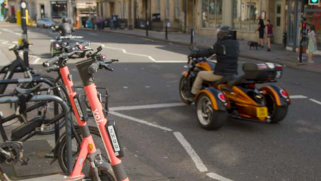 Close-Up-Shot-of-Electric-Scooters-as-Traffic-Goes-Past