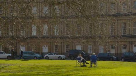 Wide-Shot-of-Senior-Couple-Sitting-On-Grass-Outside-Crescent-Housing