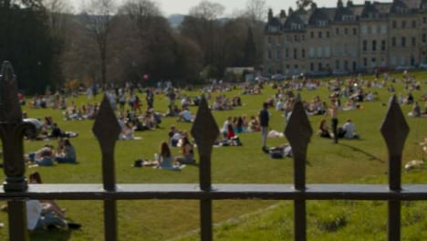 Tracking-Shot-Along-Railing-of-Busy-Royal-Crescent-Green