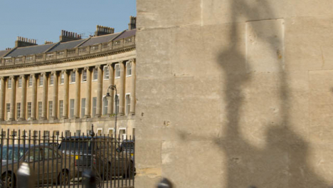 Tracking-Shot-Past-Wall-Revealing-Pedestrians-Walking-Past-Royal-Crescent