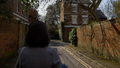 Tracking-Shot-Following-Young-Woman-Walking-Down-Quaint-Little-Street