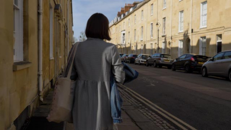 Tracking-Shot-of-Young-Woman-Walking-Around-Quiet-Street-Corner