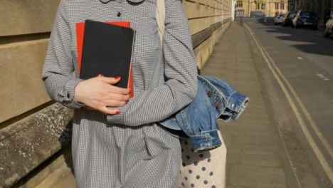 Tracking-Shot-Following-Young-Student-Holding-Books-In-Her-Hands