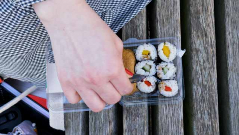 High-Angle-Shot-of-Female-Hands-Pouring-Sauce-On-Sushi