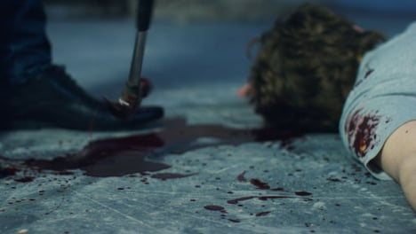 Sliding-Close-Up-Shot-of-Bloody-Hammer-Dropping-Next-to-a-Body