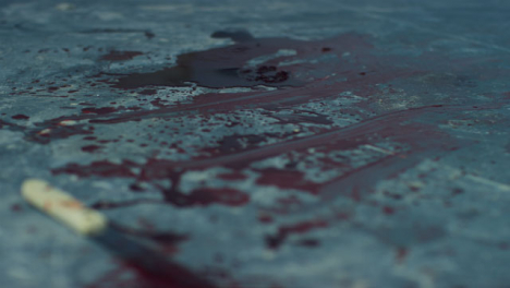 Sliding-Close-Up-Shot-of-Blood-On-Floor-of-Disused-Warehouse