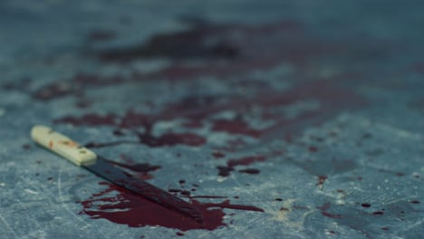 Sliding-Close-Up-Shot-of-Bloody-Knife-On-Floor-of-Disused-Warehouse