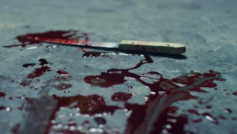 Sliding-Close-Up-Shot-of-Bloody-Knife-Scene-On-Floor-of-Disused-Warehouse