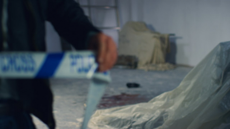 Close-Up-Shot-of-Detective-Pulling-Police-Tape-In-Disused-Warehouse