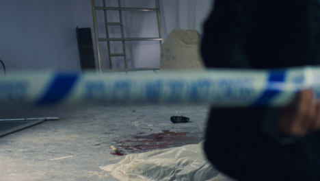 Sliding-Wide-Shot-of-Crime-Scene-In-Warehouse-with-Police-Tape-Being-Pulled-In-Foreground