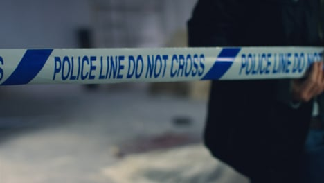 Sliding-Close-Up-Shot-of-Detective-Pulling-Police-Tape-In-Disused-Warehouse