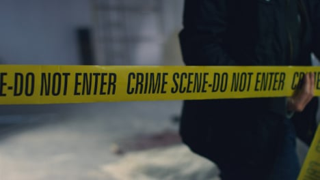 Sliding-Close-Up-Shot-of-Detective-Pulling-Across-Crime-Scene-Tape-