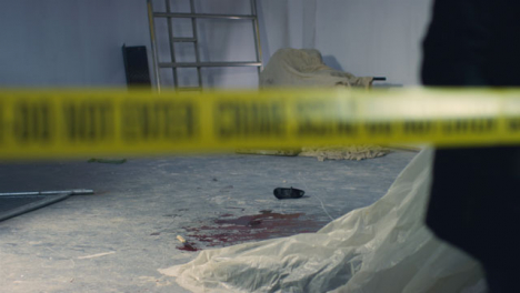 Sliding-Wide-Shot-of-Crime-Scene-In-Warehouse-with-Crime-Scene-Tape-Being-Pulled-In-Foreground