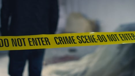 Close-Up-Shot-of-Detective-Walking-Underneath-Crime-Scene-Tape-In-Disused-Warehouse