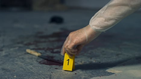 Sliding-Close-Up-of-Forensic-Placing-Evidence-Tag-Next-to-Bloody-Knife