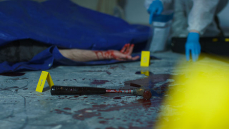 Sliding-Close-Up-of-Bloody-Hammer-with-Forensic-Placing-Evidence-Tag-In-Background-