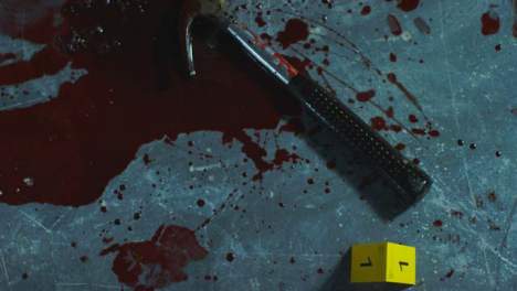 High-Angle-Shot-Looking-Down-at-a-Bloody-Hammer-at-Crime-Scene