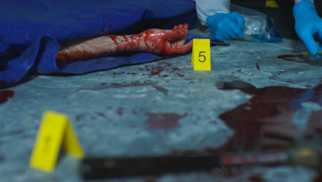 Sliding-Close-Up-Shot-of-a-Bloody-Hand-Underneath-Tarpaulin-at-Crime-Scene