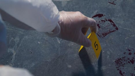 Over-the-Shoulder-Shot-of-Evidence-Tag-Being-Placed-Next-to-Bloody-Footprint-