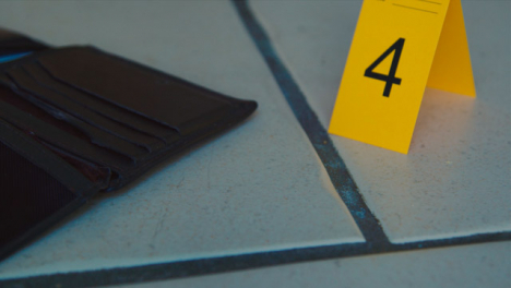 Sliding-Extreme-Close-Up-Shot-of-Evidence-Tags-On-Floor-Next-to-Broken-Glass-and-Wallet