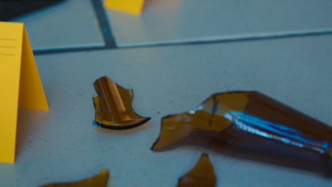 Sliding-Extreme-Close-Up-Shot-of-Evidence-Tags-On-Floor-Next-to-Broken-Bottle-and-Wallet