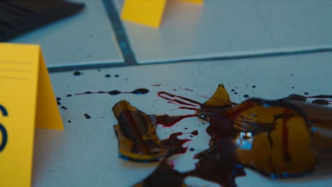 Sliding-Extreme-Close-Up-Shot-of-Evidence-Tags-On-Floor-Next-to-Bloody-Broken-Bottle