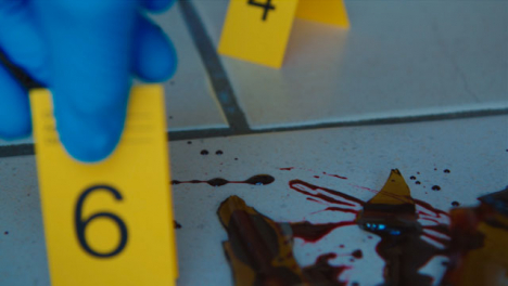 Sliding-Extreme-Close-Up-Shot-of-Evidence-Tags-On-Floor-Next-to-a-Bloody-Broken-Bottle