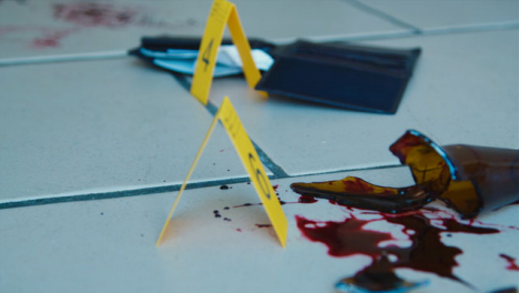 Sliding-Close-Up-Shot-of-Evidence-Tags-On-Floor-Next-to-Bloody-Broken-Bottle