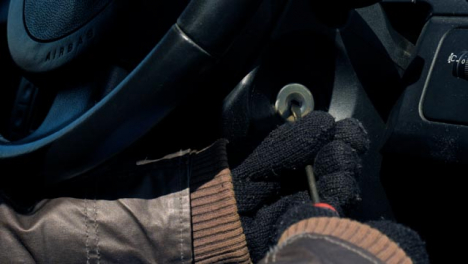 Sliding-Close-Up-Shot-of-Thief-Attempting-to-Access-Car-Ignition-with-Screwdriver
