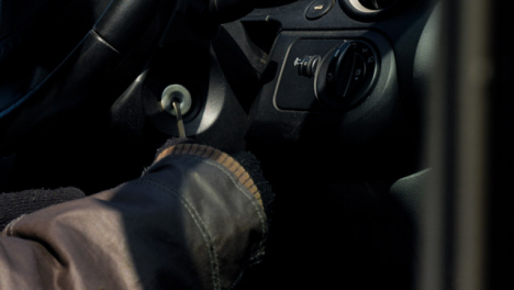 Long-Shot-of-Thief-Attempting-to-Access-Car-Ignition-with-Screwdriver