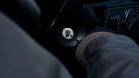Over-the-Shoulder-Shot-of-Thief-Attempting-to-Access-Car-Ignition-with-Screwdriver