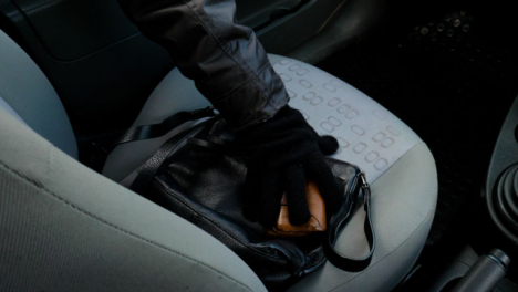 Panning-High-Angle-Shot-of-Handbag-and-Purse-Being-Stolen-from-a-Car-Seat