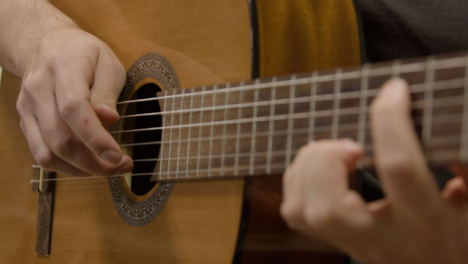 Panning-Shot-of-Musicians-Hands-Playing-Acoustic-Guitar