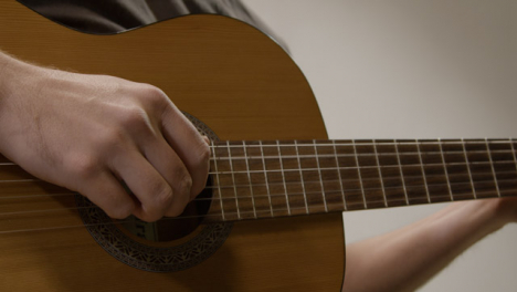 Tracking-Shot-Pulling-Out-Revealing-Musicians-Hand-Playing-Acoustic-Guitar