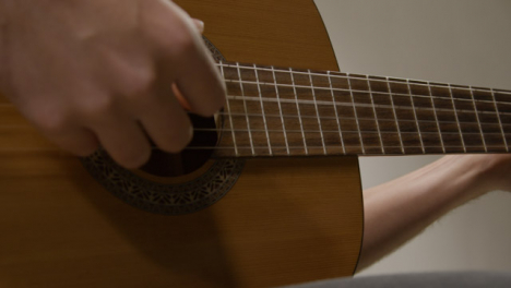 Tracking-Shot-Approaching-a-Musicians-Hand-Plucking-Acoustic-Guitar-Strings