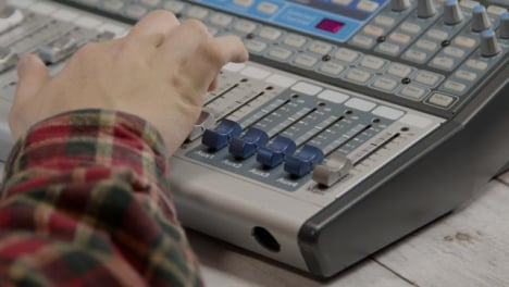 Tracking-Shot-of-a-Sound-Mixers-Hand-Adjusting-Fader-Switches