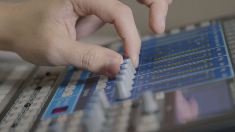 Close-Up-Shot-of-Sound-Mixers-Hand-Adjusting-Sound-Board-Knobs