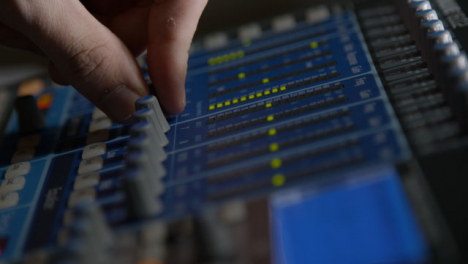 Close-Up-Shot-of-Sound-Mixers-Hand-Adjusting-Knobs-On-a-Sound-Board
