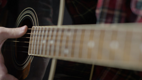 Pull-Focus-Shot-from-Fret-Board-to-Acoustic-Guitar-Body-as-Musician-Plays