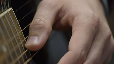 Sliding-Extreme-Close-Up-Shot-of-Musicians-Hands-Playing-Acoustic-Guitar