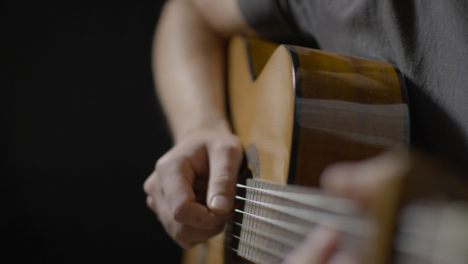 Sliding-Close-Up-Shot-Approaching-Acoustic-Guitar-Body-as-Musician-Plays-