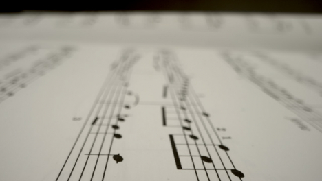 Tracking-Shot-Over-Bars-On-Music-Sheet-Book-Page-