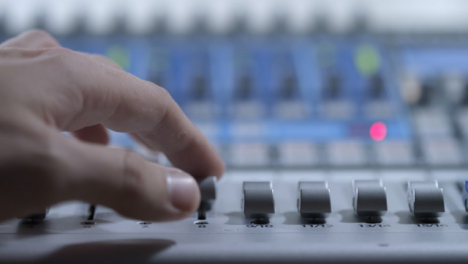 Close-Up-Shot-of-Audio-Mixers-Hand-Adjusting-Faders-On-Audio-Mixing-Board
